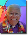 Paul Egertson smiling holding a rainbow umbrella and wearing a rainbow print stole around his neck