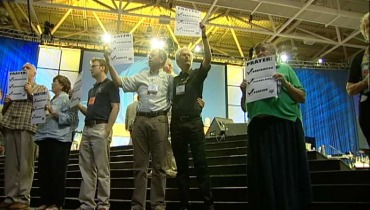 Participants in an action at the PC(USA) General Assembly hold signs before being arrested